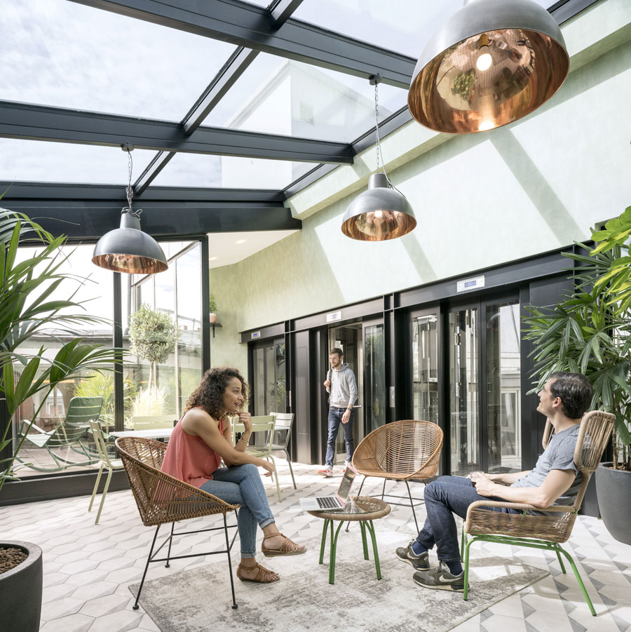 Users step out of the elevator into a conservatory space.