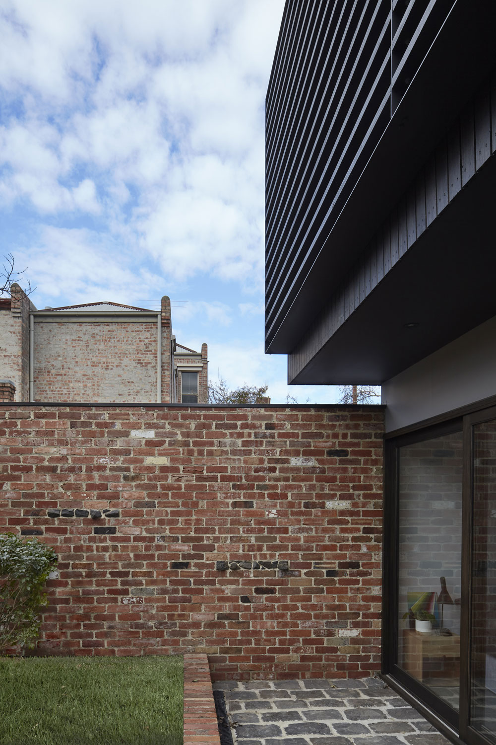 The recycled brick wall extends out from the house enclosing the garden from the laneway.