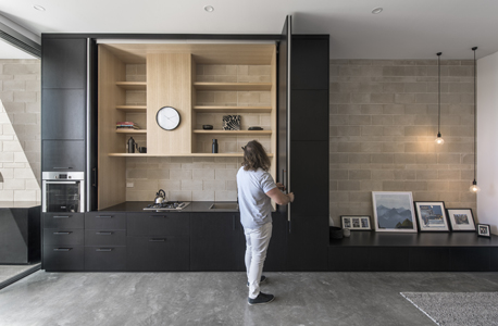 Black cabinet doors reveal a kitchen