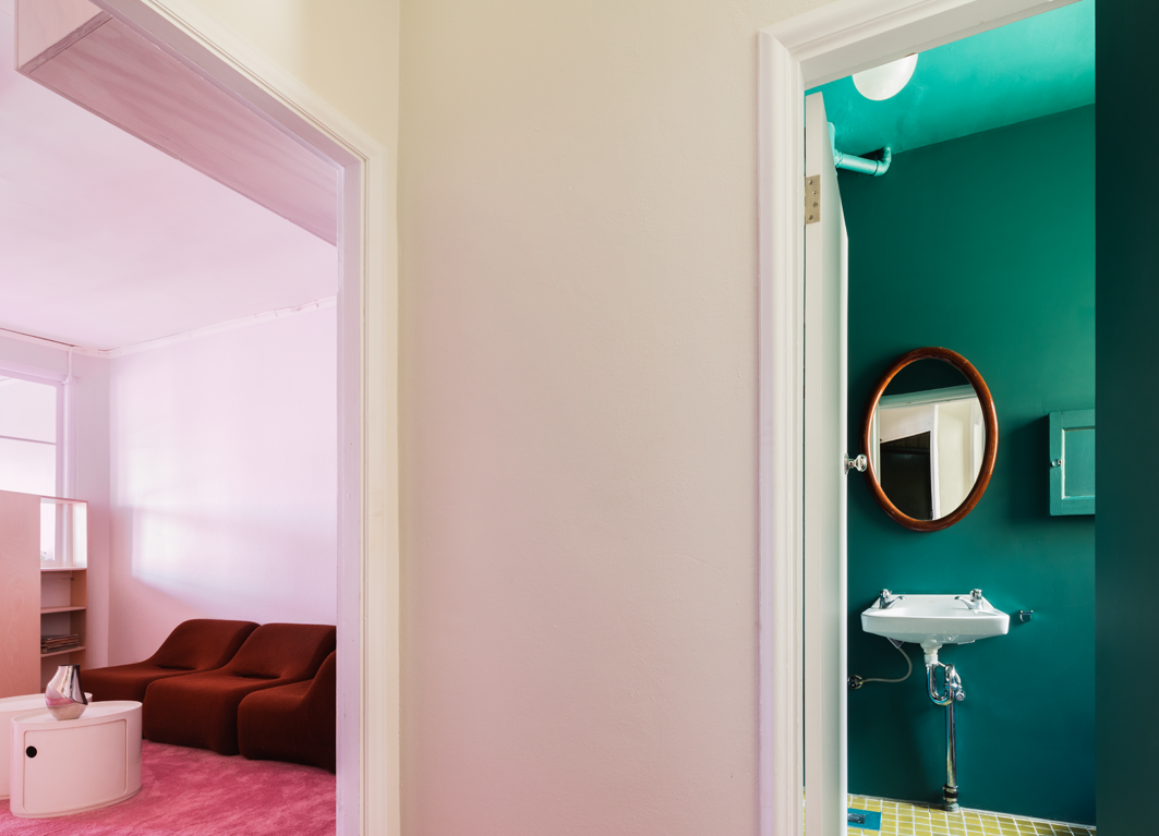 Mid-afternoon light transforms the interior from white to pink, while an emerald bathroom provides a striking contrast