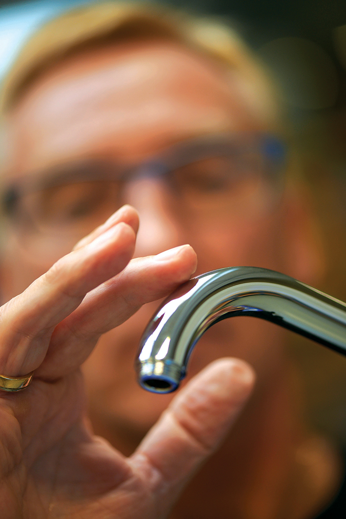 A designer inspects a VOLA tap