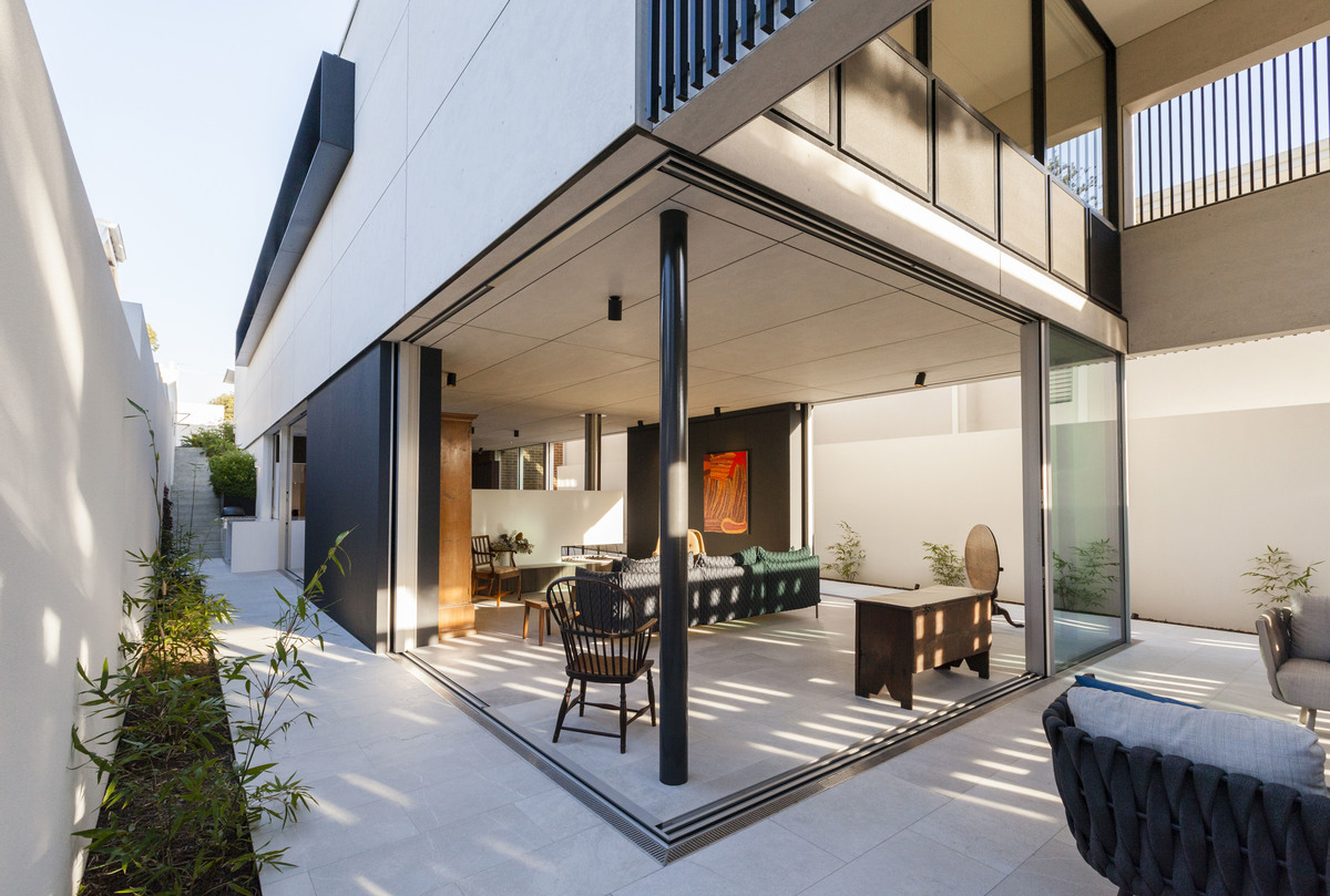 The walls of the glass box retract into wall cavities allowing the living and dining spaces of this house to expand beyond to the boundary walls