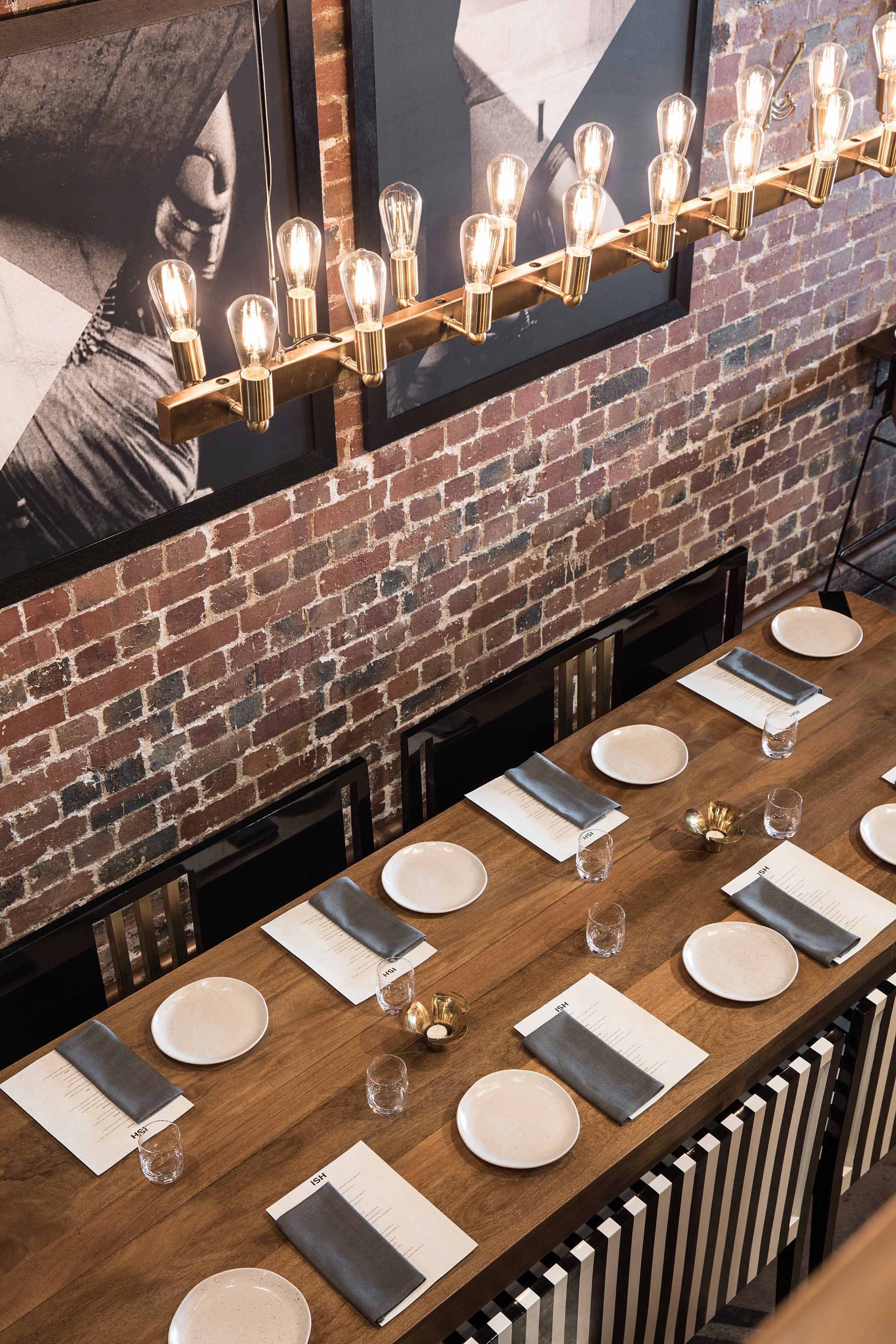 A long communal table and bespoke black and white-striped pews