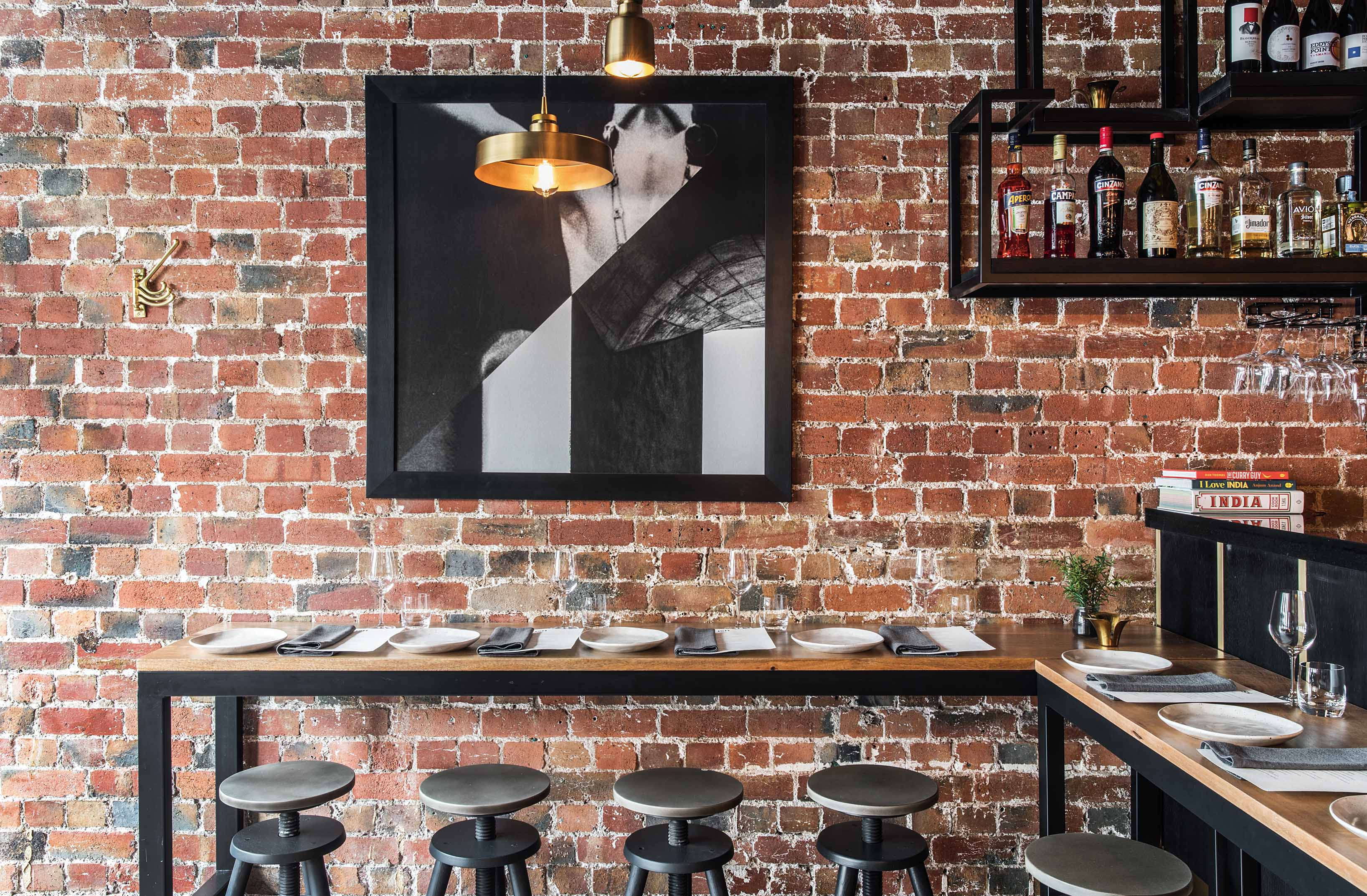 High hardwood timber tables line the exposed brick wall