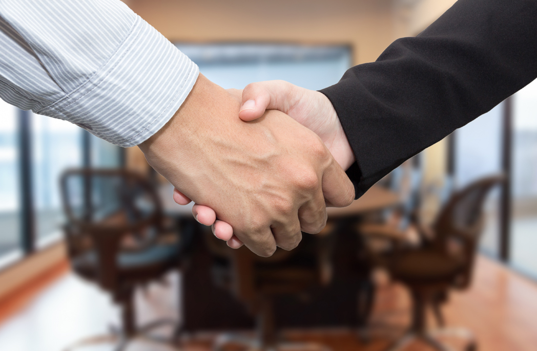 Close up of businessmen shaking hands in meeting room.
