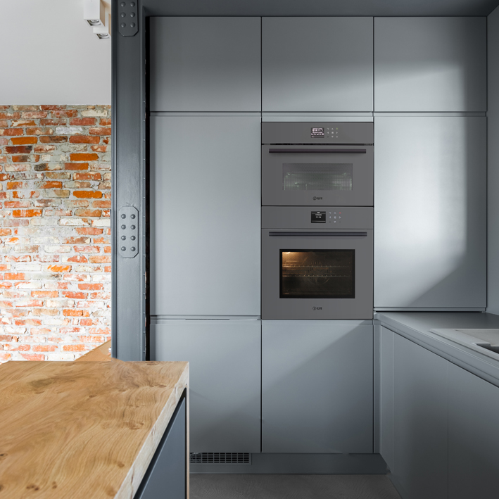 Gray kitchen wall with built-in oven and microwave